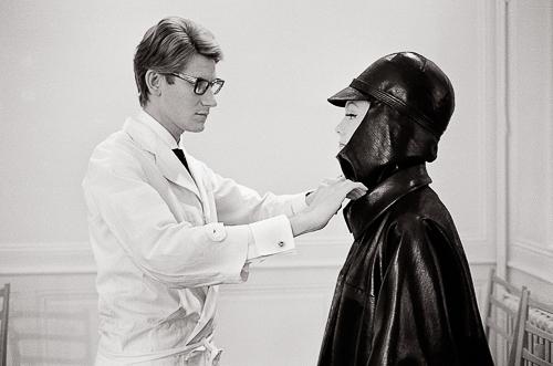 France, Paris, 26 juillet 1963, pour sa collection Automne-Hiver, le créateur Yves Saint-Laurent crée un imperméable de ciré noir, casquette-cagoule et cuissardes, portés par un mannequin sur lequel il ajuste le col. Il porte une blouse blanche.